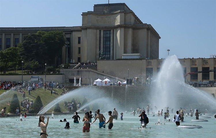 Người dân giải nhiệt tại một đài phun nước ở Paris ngày 26/6.