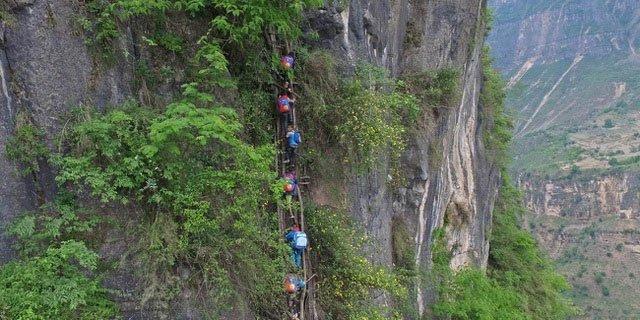 Cảnh trẻ nhỏ trong làng leo trên thang gỗ chênh vênh để xuống núi