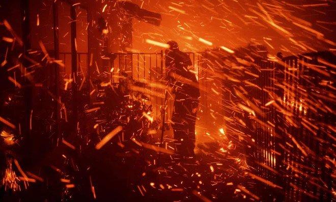 Một người đàn ông cố gắng dùng vòi nước dập lửa để cứu ngôi nhà của mình khỏi đám cháy