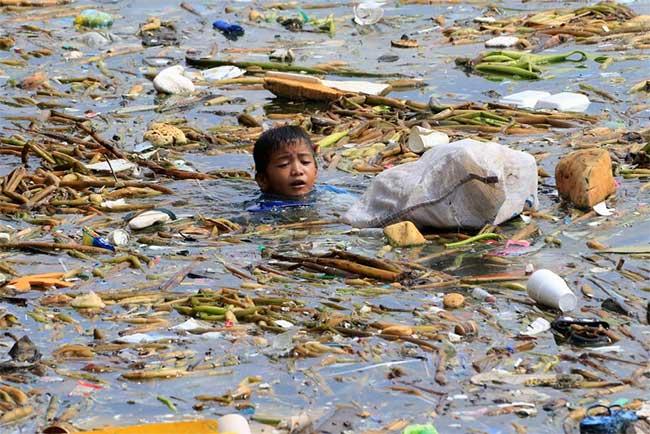 Một cậu bé theo gia đình làm nghề thu lượm ve chai, đang bơi lội giữa vùng nước biển ngập ngụa rác