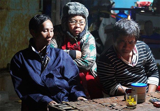 Ông Nguyễn Đúng (bìa trái) cùng các thành viên trong gia đình theo dõi diễn biến bão qua điện thoại.