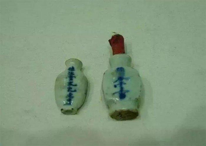 Các chuyên gia mở chiếc hộp vàng và tìm thấy một chai bằng sứ nhỏ ở trong với chiếc nút vải.